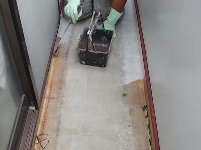 画像:施行中 ガラスマットの上にエポキシ樹脂塗料を塗っていく