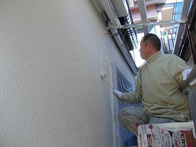 画像:施行中 吹き付けた塗料が乾燥した後、仕上げ色による塗装のためのシーラー塗布