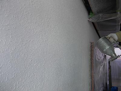画像:施行中 弾性の塗料で既存の外壁と同じ模様になるよう吹き付け塗装を行う
