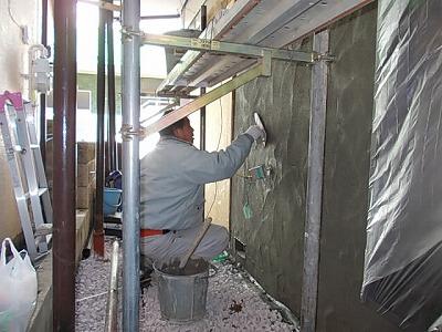画像:施行中 外壁にモルタル塗り付け中(中塗り)